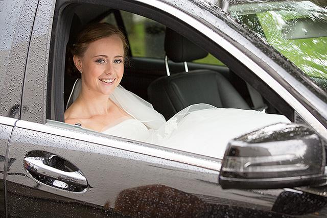 Bruden gjemmer for seg regnet i pappas bil