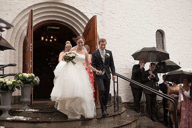 De nygifte kommer ut i regnet på kirketrappen