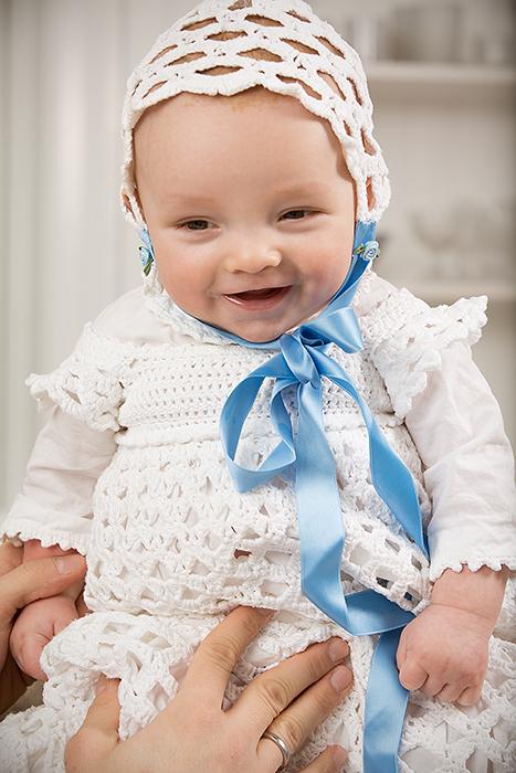 En veldig blid gutt, fotografert i dåpskjolen sin