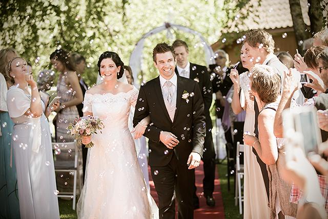 De nygifte går ned midtgangen mens gjestene blåser såpebobler